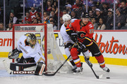 T.J. Galiardi #39 of the Calgary Flames looks for a wrap-around as Jonas Hiller #1 (L) and Ben Lovejoy #6 of the Anaheim Ducks defend during an NHL game at Scotiabank Saddledome on March 26, 2014 in Calgary, Alberta, Canada. The Ducks defeated the Flames 3-2.