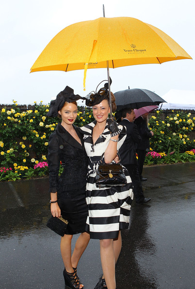 Anthea Crebbin Models Lucy Mcintosh and Anthea Crebbin shelter under an umbrella in the rain at AAMI Victoria Derby Day at Flemington Racecourse on October 30, 2010 in Melbourne, Australia.