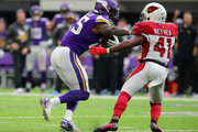 Latavius Murray #25 of the Minnesota Vikings runs with the ball and stiff arms Antoine Bethea #41 of the Arizona Cardinals on the way to a 21-yard touchdown at U.S. Bank Stadium on October 14, 2018 in Minneapolis, Minnesota.