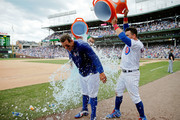 Albert Almora Jr. #5 and Kyle Schwarber #12 (R) of the Chicago Cubs douse Anthony Rizzo #44 after his walk-off home run in a win over the Arizona Diamondbacks at Wrigley Field on July 26, 2018 in Chicago, Illinois. The Chicago Cubs won 7-6.
