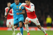 Alexis Sanchez of Arsenal takes on Dani Alves of Barcelona during the UEFA Champions League round of 16 first leg match between Arsenal and Barcelona on February 23, 2016 in London, United Kingdom.