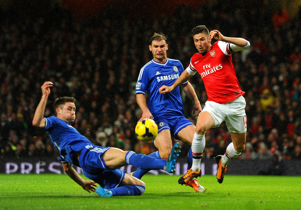 Gary Cahill of Chelsea tackles Olivier Giroud of Arsenal