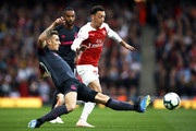 Lucas Digne of Everton tackles Mesut Ozil of Arsenal during the Premier League match between Arsenal FC and Everton FC at Emirates Stadium on September 23, 2018 in London, United Kingdom.