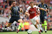 Aaron Ramsey of Arsenal is challenged by Aymeric Laporte of Manchester City during the Premier League match between Arsenal FC and Manchester City at Emirates Stadium on August 12, 2018 in London, United Kingdom.