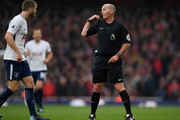 Referee Mike Dean reacts during the Premier League match between Arsenal and Tottenham Hotspur at Emirates Stadium on November 18, 2017 in London, England.