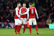 Aaron Ramsey of Arsenal talks to Calum Chambers and Granit Xhaka of Arsenal during the Carabao Cup Final between Arsenal and Manchester City at Wembley Stadium on February 25, 2018 in London, England.