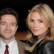 She smiles with Topher Grace.