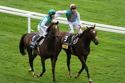 Tom Queally riding Frankel (R) celebrates winning The Qipco Champion Stakes with Ian Mongan riding Bullet Train (L) at Ascot racecourse on October 20, 2012 in Ascot, England.