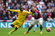 Mario Balotelli of Liverpool and Ron Vlaar of Aston Villa tussle for the ball during the FA Cup Semi Final between Aston Villa and Liverpool at Wembley Stadium on April 19, 2015 in London, England.