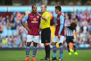 Gabriel Agbonlahor (L) of Aston Villa talks to referee Mike Dean with Ashley Westwood of Aston Villa during the Barclays Premier League match between Aston Villa and Newcastle United at Villa Park on August 23, 2014 in Birmingham, England.