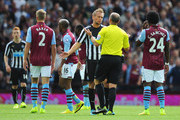 Referee Mike Dean is confronted by Siem de Jong of Newcastle United after sending off Mike Williamson of Newcastle United during the Barclays Premier League match between Aston Villa and Newcastle United at Villa Park on August 23, 2014 in Birmingham, England.