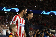 Diego Costa of Atletico Madrid and Cristiano Ronaldo of Juventus walk out onto the pitch prior to the UEFA Champions League group D match between Atletico Madrid and Juventus at Wanda Metropolitano on September 18, 2019 in Madrid, Spain.