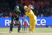 Brad Haddin of Australia drives with Maurice Ouma of Kenya looking on during the 2011 ICC World Cup Group A match between Australia and Kenya at M. Chinnaswamy Stadium on March 13, 2011 in Bangalore, India.