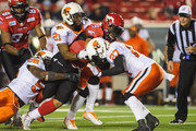 Jon Cornish #9 of the Calgary Stampeders runs the ball as Solomon Elimimian #56, Ryan Phillips #21 and J.R. LaRose #27 of the BC Lions try to stop him during a CFL game at McMahon Stadium on September 27, 2014 in Calgary, Alberta, Canada. The Stampeders defeated the Lions 14-7.