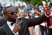 """Congolese-born French rapper Maitre Gims takes photos as he arrives on May 14, 2016 for the screening of the film """"The BFG"""" at the 69th Cannes Film Festival in Cannes, southern France.  / AFP / LOIC VENANCE"""