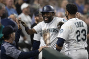 Denard Span #4 (C) of the Seattle Mariners is congratulated by hitting coach Edgar Martinez and Nelson Cruz #23 of the Seattle Mariners after hitting solo home run against starting pitcher Andrew Cashner #54 of the Baltimore Orioles during the fifth inning of a game at Safeco Field on September 5, 2018 in Seattle, Washington.