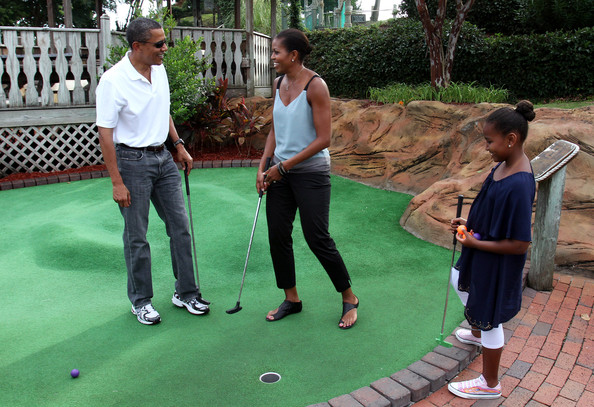 Barack Obama (AFP OUT) United States President Barack Obama and first lady Michelle Obama play miniature golf with daughter Sasha at Pirate's Island Miniature Golf August 14, 2010 in Panama City Beach, Florida. The First Family is visiting the area to help promote tourism and check up on clean up efforts from the aftermath of the Deepwater Horizon Oil spill.
