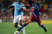 Gai (R) of Barcelona duels for the ball with Kelvin Etuhu of Manchester City during the Joan Gamper Trophy match between Barcelona and Manchester City at the Camp Nou Stadium on August 19, 2009 in Barcelona, Spain. Manchester City won the match 1-0.
