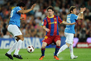 Lionel Messi (C) of Barcelona duels for the ball with Santiago Acasiete (L) of Almeria as Angel Garcia appeals for a hands ball during the la Liga match between FC Barcelona and UD Almeria at the Camp Nou stadium on April 9, 2011 in Barcelona, Spain.