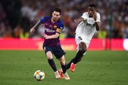 Lionel Messi of FC Barcelona competes for the ball with Geoffrey Kondogbia of Valencia CF during the Spanish Copa del Rey match between Barcelona and Valencia at Estadio Benito Villamarin on May 25, 2019 in Seville, Spain.