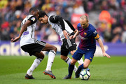 Andres Iniesta of FC Barcelona competes for the ball with Geoffrey Kondogbia (L) Carlos Soler of Valencia CF during the La Liga match between Barcelona and Valencia at Camp Nou on April 14, 2018 in Barcelona, Spain.