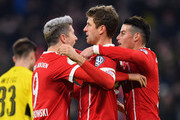 Thomas Mueller of Bayern Muenchen celebrates after scoring his sides second goal with Robert Lewandowski of Bayern Muenchen and James Rodriguez of Bayern Muenchen during the DFB Cup match between Bayern Muenchen and Borussia Dortmund at Allianz Arena on December 20, 2017 in Munich, Germany.