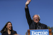 Democratic presidential candidate, Sen. Bernie Sanders (I-VT) waves with Rep. Alexandria Ocasio-Cortez (D-NY) as she endorses him during his speech at a campaign rally in Queensbridge Park on October 19, 2019 in the Queens borough of New York City.  This is Sanders' first rally since he paused his campaign for the nomination due to health problems.