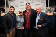 (L-R) Adam Richman, Anne Burrell, Nick Mangold  and Andrew Zimmern pose in front of the judges table at the Blue Moon Burger Bash presented by Pat LaFrieda Meats hosted by Rachael Ray during the New York City Wine & Food Festival at Esurance Rooftop Pier 92 on October 17, 2014 in New York City.
