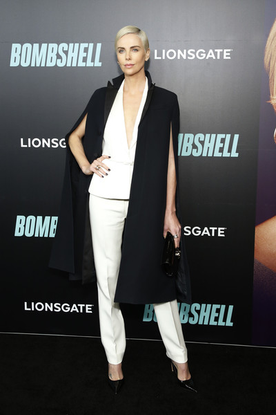 Charlize Theron topped off her suit with a black cape.