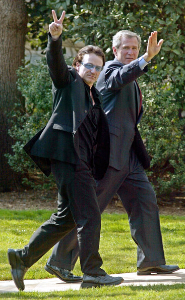 Bono 402323 01: U.S. President George W. Bush (R) waves as Bono, the lead singer of Irish pop group U2, makes a V sign as they walk toward the Oval Office of the White House March 14, 2002 in Washington, DC. Bono returned to the White House after they attended an Inter-American Development Bank event on global development in Washington.