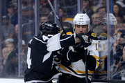 Milan Lucic #17 of the Boston Bruins takes a check from Robyn Regehr #44 of the Los Angeles Kings during the first period at Staples Center on December 2, 2014 in Los Angeles, California.