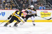 Brad Marchand #63 of the Boston Bruins skates with the passes the puck past Justin Schultz #4 of the Pittsburgh Penguins at PPG PAINTS Arena on January 7, 2018 in Pittsburgh, Pennsylvania.