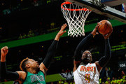 Paul Millsap #4 of the Atlanta Hawks lays in a basket against Jared Sullinger #7 of the Boston Celtics in Game One of the Eastern Conference Quarterfinals during the 2016 NBA Playoffs at Philips Arena on April 16, 2016 in Atlanta, Georgia.  NOTE TO USER User expressly acknowledges and agrees that, by downloading and or using this photograph, user is consenting to the terms and conditions of the Getty Images License Agreement.
