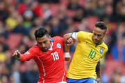 Gonzalo Jara of Chile and Neymar of Brazil comnpete for the ball during the international friendly match between Brazil and Chile at the Emirates Stadium on March 29, 2015 in London, England.