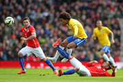 Willian of Brazil is tackled by Gonzalo Jara of Chile during the international friendly match between Brazil and Chile at the Emirates Stadium on March 29, 2015 in London, England.