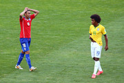 Gonzalo Jara of Chile and Willian of Brazil react during the 2014 FIFA World Cup Brazil round of 16 match between Brazil and Chile at Estadio Mineirao on June 28, 2014 in Belo Horizonte, Brazil.