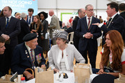 British Prime Minister Theresa May (C) chats with veteran Leslie Stocking (2L) as her husband Philip May (CR) looks on, following a service of remembrance at Bayeux cemetery on June 06, 2019 in Bayeux, France. Veterans and families gathered in Normandy to commemorate D-Day's 75th anniversary. It has been announced that 16 countries had signed a historic proclamation of peace to ensure the horrors of the Second World War are never repeated. The text has been agreed by Australia, Belgium, Canada, Czech Republic, Denmark, France, Germany, Greece, Luxembourg, Netherlands, Norway, New Zealand, Poland, Slovakia, the United Kingdom and the United States of America.