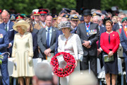 Britain's Prime Minister, Theresa May lays a wreath at Bayeux War Cemetery during a memorial service on June 06, 2019 in Bayeux, France. Veterans, families, visitors, political leaders and military personnel are gathering in Normandy to commemorate D-Day, which heralded the Allied advance towards Germany and victory about 11 months later.