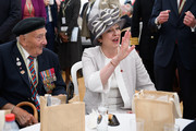 British Prime Minister Theresa May (R) waves to another man as she chats with veteran Leslie Stocking (L), following a service of remembrance at Bayeux cemetery on June 06, 2019 in Bayeux, France. Veterans and families gathered in Normandy to commemorate D-Day's 75th anniversary. It has been announced that 16 countries had signed a historic proclamation of peace to ensure the horrors of the Second World War are never repeated. The text has been agreed by Australia, Belgium, Canada, Czech Republic, Denmark, France, Germany, Greece, Luxembourg, Netherlands, Norway, New Zealand, Poland, Slovakia, the United Kingdom and the United States of America.