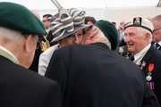 British Prime Minister Theresa May (CL) is kissed by veteran Robert Yaxley (CR) following a service of remembrance at Bayeux cemetery on June 06, 2019 in Bayeux, France. Veterans and families gathered in Normandy to commemorate D-Day's 75th anniversary. It has been announced that 16 countries had signed a historic proclamation of peace to ensure the horrors of the Second World War are never repeated. The text has been agreed by Australia, Belgium, Canada, Czech Republic, Denmark, France, Germany, Greece, Luxembourg, Netherlands, Norway, New Zealand, Poland, Slovakia, the United Kingdom and the United States of America.