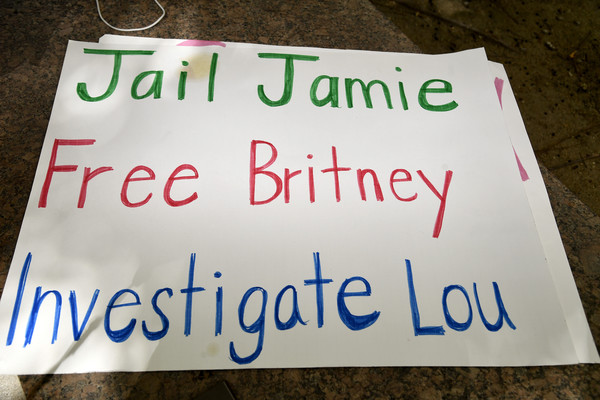 #FreeBritney Protest Outside Courthouse In Los Angeles During Conservatorship Hearing [text,font,signage,banner,sign,britney spears,james spears,sign,conservatorship,los angeles,freebritney protest outside courthouse,courthouse,conservatorship hearing,hearing,protest,banner,meter,traffic sign]