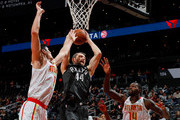 Tyler Zeller #44 of the Brooklyn Nets grabs a rebound against Ersan Ilyasova #7 and Dewayne Dedmon #14 of the Atlanta Hawks at Philips Arena on January 12, 2018 in Atlanta, Georgia.  NOTE TO USER: User expressly acknowledges and agrees that, by downloading and or using this photograph, User is consenting to the terms and conditions of the Getty Images License Agreement.