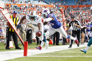 Reggie Bush #22 of the Miami Dolphins scores a touchdown while being defended by Kelvin Sheppard #55 of the Buffalo Bills on December 23, 2012 at Sun Life Stadium in Miami Gardens, Florida.