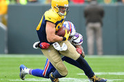 Jimmy Graham #80 of the Green Bay Packers is tackled by Tremaine Edmunds #49 of the Buffalo Bills during the third quarter of a game at Lambeau Field on September 30, 2018 in Green Bay, Wisconsin.