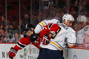 Jon Merrill #7 of the New Jersey Devils and Cody McCormick #8 of the Buffalo Sabres gets tangled up during the first period at the Prudential Center on January 6, 2015 in Newark, New Jersey.