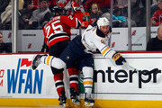 Seth Helgeson #25 of the New Jersey Devils is hit into the boards by Cody McCormick #8 of the Buffalo Sabres during the second period at the Prudential Center on January 6, 2015 in Newark, New Jersey.