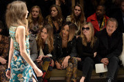 (L-R) Cara Delevingne, Jourdan Dunn, Kate Moss and Mario Testino attend the Burberry Prorsum AW 2015 show during London Fashion Week at Kensington Gardens on February 23, 2015 in London, England.