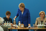 German Chancellor and leader of the German Chistian Democrats (CDU) Angela Merkel pours coffee as she for an early morning meeting of the CDU governing board ascolleagues Annegret Kramp-Karrenbauer (L) and Julia Kloeckner look on on July 2, 2018 in Berlin, Germany. German Interior Minister and leader of the Bavarian sister party of the CDU, the CSU, Horst Sehhofer, had announced he will resign yesterday from both posts over what he sees as insufficient policy by Merkel over asylum and migraiton policy. He then announced he will postpone his resignation in order to meet with Merkel later today.