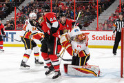 David Rittich #33 of the Calgary Flames has the puck go off his face-mask as Jean-Gabriel Pageau #44 and Mark Stone #61 of the Ottawa Senators look for the rebound in the second period at Canadian Tire Centre on March 9, 2018 in Ottawa, Ontario, Canada.