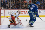 Goalie Mike Smith #41 of the Calgary Flames makes a save while Jake Virtanen #18 of the Vancouver Canucks tries to screen in NHL action on October, 3, 2018 at Rogers Arena in Vancouver, British Columbia, Canada.